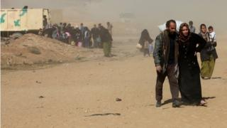 An Iraqi man and woman, who look to be struggling, walk amid dust and sand as they flee their homes in west Mosul. Dozens of people, including children are seen behind them.