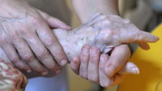 Elderly person's hand being held