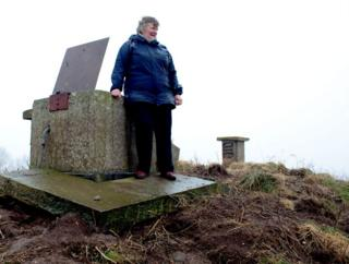 Rosemary 'Christine' Wright stands next to the entrance of a bunker monitoring post on the East Yorkshire Coast