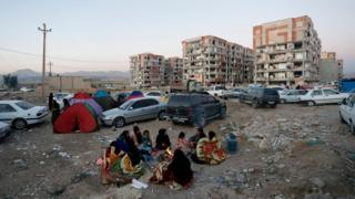 Iranian people don arrange small-small camps outside buildings wey di earthquake destroy, for Pole-Zahab, Kermanshah province, on 13 Nov 2017
