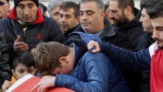 أولاس أريك (في الوسط) يبكي على فقدان والده يوم تشييع الجنازة