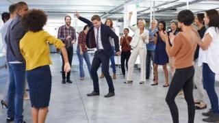 Una persona bailando en medio de un círculo de colegas en la oficina