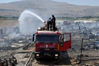 Bomberos apagan el fuego en un campamento de refugiados sirios en el valle de Bekaa, en Líbano.