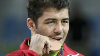 Güreşçi Cenk İldem, kazandığı bronz madalyayı ısırarak poz veriyor.