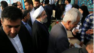 Hassan Rouhani surrounded by people at a polling station