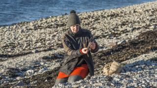 Artist Julia Barton gathering plastic from a beach