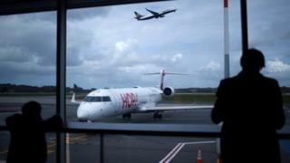 Passengers are seen in silhouette as at Nantes airport