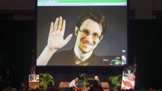 Edward Snowden smiles and waves from a huge screen set up in a conference hall full of people