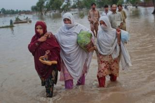 Three women in Pakistan wade through floodwater, carrying their belongings