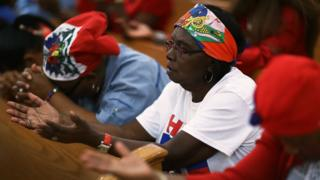 "Parishioners pray together during a service at the Notre Dame D""Haiti Catholic Church as they celebrate Haitian Flag day in the Little Haiti neighborhood on May 18, 2017 in Miami, Florida."