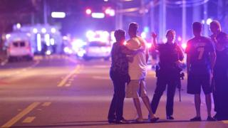 Orlando police officers direct family members away from a fatal shooting at Pulse Orlando nightclub in Orlando, Florida - 12 June 2016