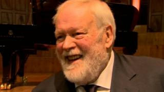 Michael Longley sitting in front of a piano