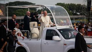 Pope Francis gets into a vehicle upon his arrival at Yangon International Airport