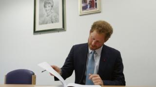 Prince Harry signs a visitors book