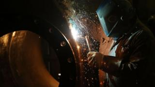 Welder working on a tank for fracking