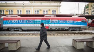 "A man passes a train decorated with the Serbian flag and the words ""Kosovo is Serbia"" in Belgrade."