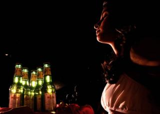 Indian models gestures as she holds bottles of Kingfisher beer during the launch of commemorative packs of 'Indian October Fest' beer bottles