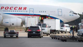 Vehicles pull up to a Russian aircraft to load freight at Dulles International Airport December 31, 2016, in Sterling, Virginia, just outside Washington, DC.