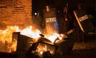 Spanish police officers stand close to burning bins in Madrid's Lavapies district