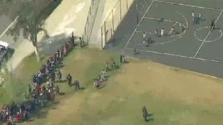 Aerial footage of children being evacuated from a primary school in San Bernardino, California, following a shooting, 10 April 2017