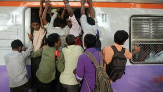 Commuters attempt to board a train in Mumbai