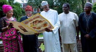 A photograph tweeted by the @NGRPresident Twitter account shows President Buhari standing outdoors, grinning and wearing sunglasses while holding a large get well card, with a handful of officials around him.