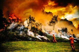 Firefighters battle a blaze on a hill