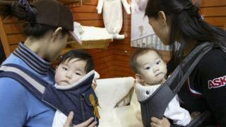 Two mothers carrying their babies while at a baby fair