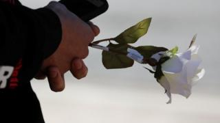 A rose is held in memory of those killed in the Las Vegas mass shooting on 1 October, 2017