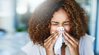 A woman sneezes