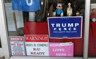 Shop window with Trump signs, a Mickey Mouse figure and an image of the Pope