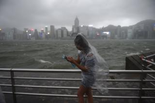 A woman uses her phone while wearing a plastic poncho along Victoria Harbour during heavy winds and rain brought on by Typhoon Hato in Hong Kong on 23 August 2017.