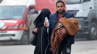 A man carries a child with an IV drip as he flees deeper into the remaining rebel-held areas of Aleppo, Syria December 12, 2016.