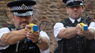 Two police officers using Taser guns