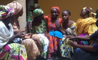 Une fille de Chibok entourée par les membres de sa famille