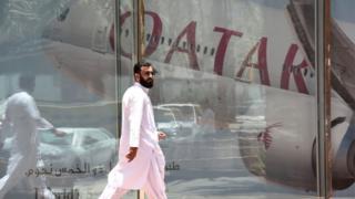 सऊदी अरब में क़तर एयरवेज़ के दफ़्तार के सामने से गुज़रते एक व्यक्ति