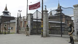 Indian paramilitary troopers stand guard outside Jamia Masjid during a curfew and strike called following the killing of a Kashmiri student in downtown Srinagar on June 9, 2017