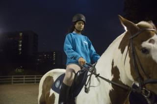 A young woman rides a horse at night
