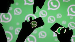 Pessoas com celulares que mostram o logo do WhatsApp