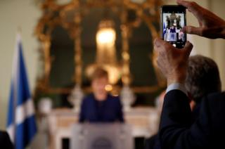 A man uses a mobile phone to photograph Nicola Sturgeon