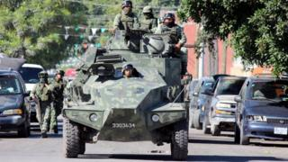 Soldiers patrol atop a vehicle along a street near a crime scene where the body of a man, who witnesses said was tossed from a plane, landed on a hospital roof in Culiacan, in Mexico's northern Sinaloa state April 12, 2017