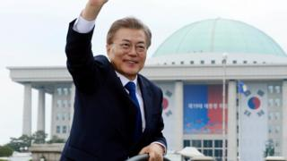 新任总统文在寅乘车离开韩国国会大楼时向群众挥手(10/5/2017)