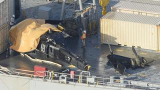 """A yellow sheet covers a U.S. Army helicopter U-60 that crashed on the Navy cargo vessel USNS Red Cloud in the waters around 20 miles (30 kilometers) east of Japan""""s southern island of Okinawa Wednesday, Aug. 12, 2015"""