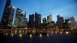 People walk past the skyline of Marina Bay central business district in Singapore 26 April 2013