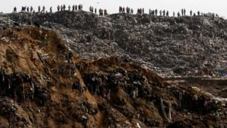 Garbage collectors look at rescue teams working at the site where a massive pile of garbage collapsed at a landfill dumpsite in Guatemala City