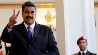 Venezuela's President Nicolas Maduro smiles to the media after a meeting, with a military officer visible nearby behind him