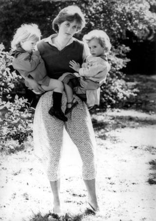 Diana holds two children as the sun shines through her skirt.