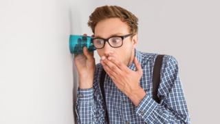 Una persona espiando una conversación con un vaso pegado a una pared