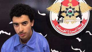 Hashem Abedi is seen next to the logo of Libya's Special Deterrence Forces in a handout photo dated May 25