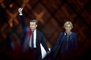 French president-elect Emmanuel Macron and his wife Brigitte Trogneux greet supporters in front of the Pyramid at the Louvre Museum in Paris